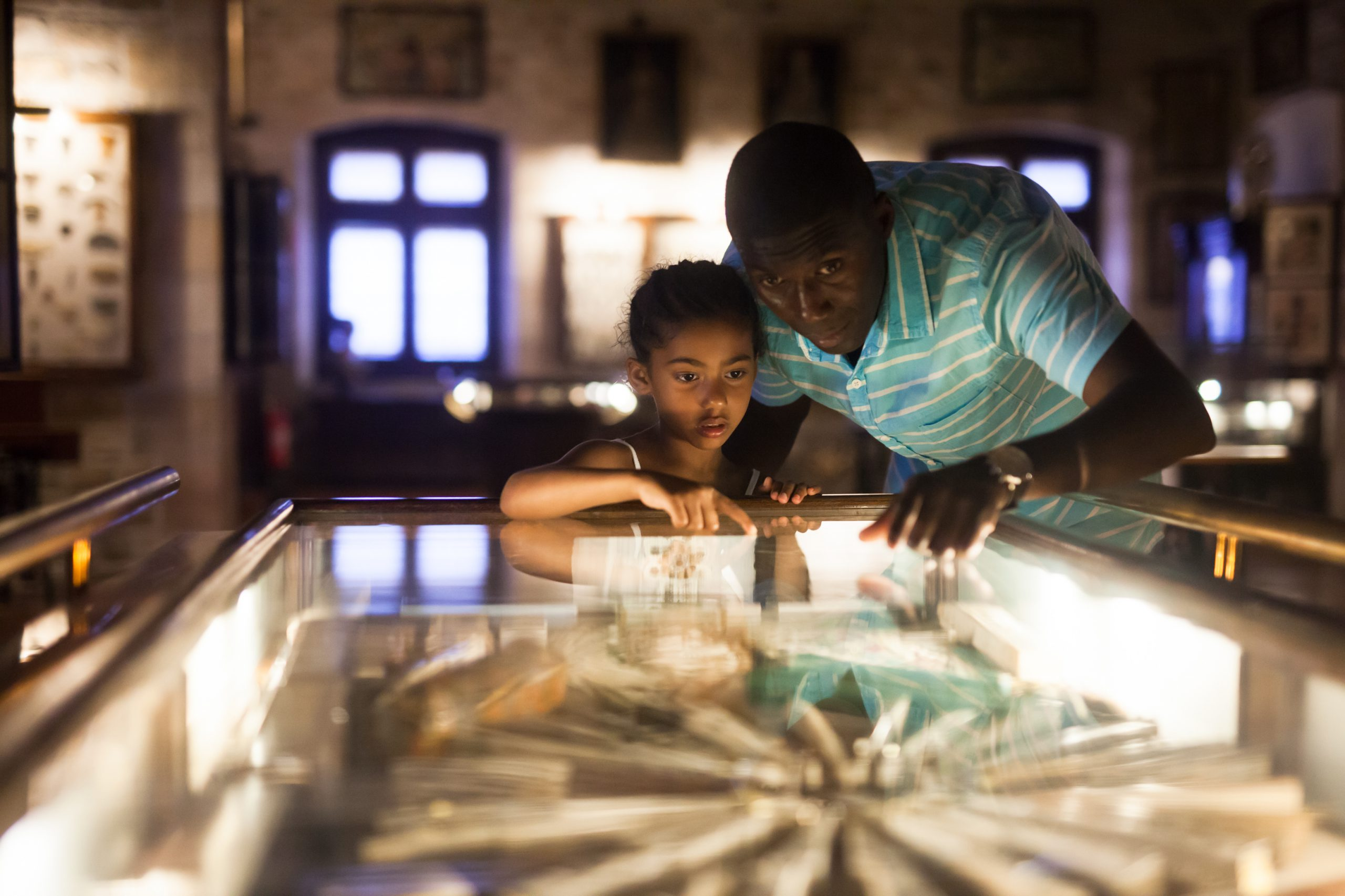 An adult and a child lean over a lit table covered with glass. They are pointing at the exhibit.