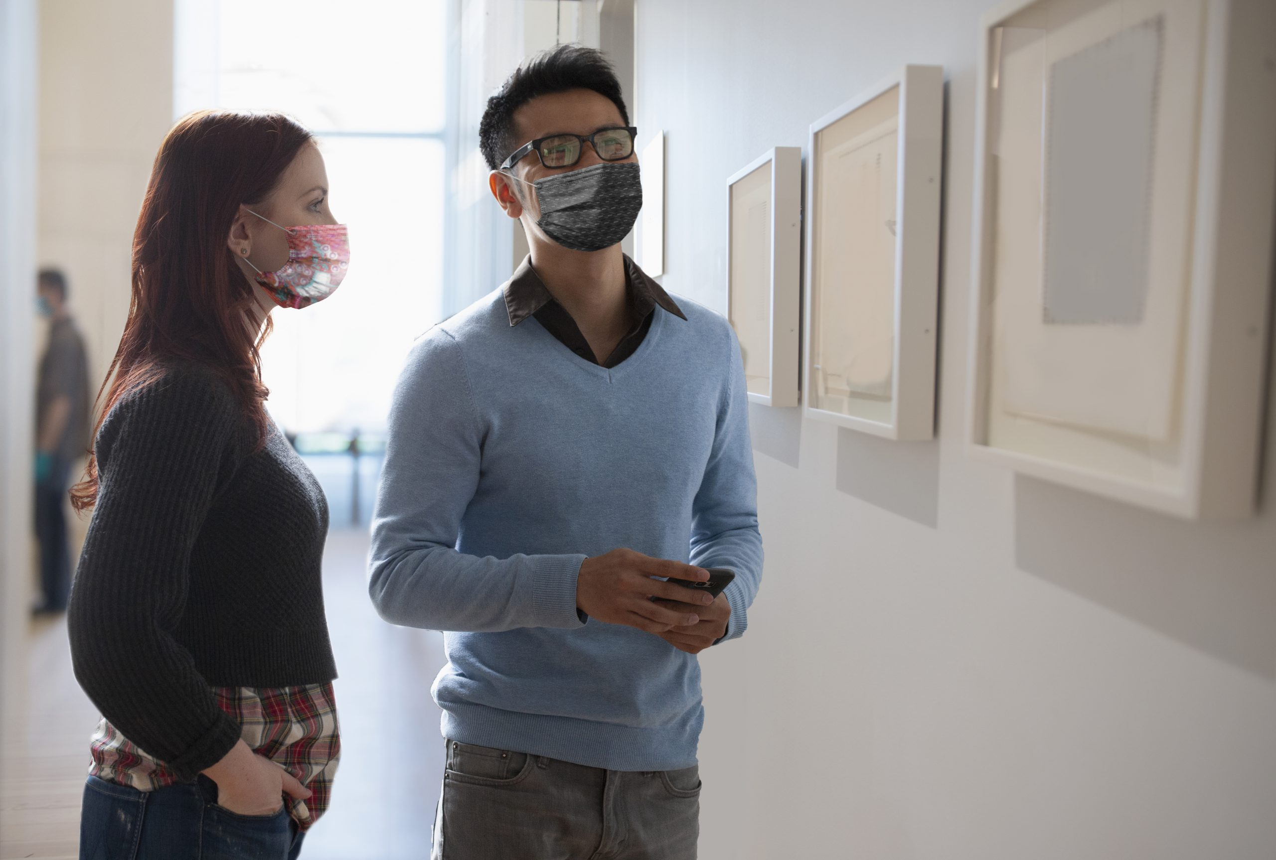 Two adults standing in front of a wall with a row of framed art.