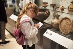 Child in front of cultural artifacts taking notes on paper.