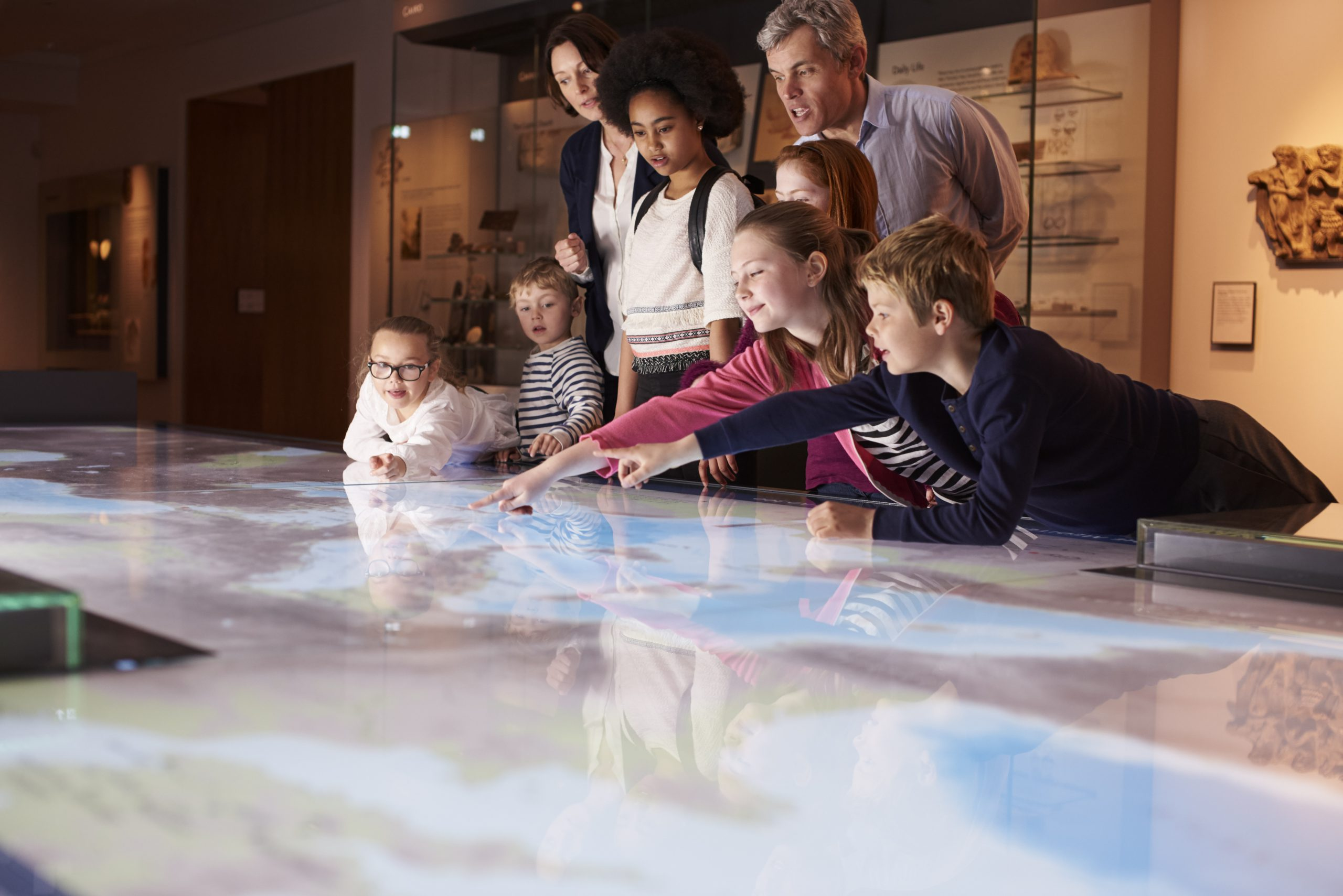 Group of adults and children looking at an interactive table. Three children are leaning over the table and pointing.