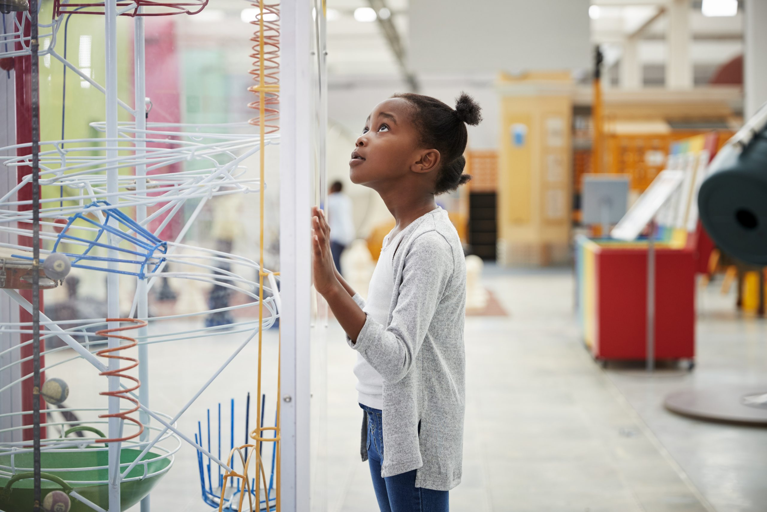 Child looking up at a clear cylindrical exhibit that contains spirals, strings, and other shapes in various colors.